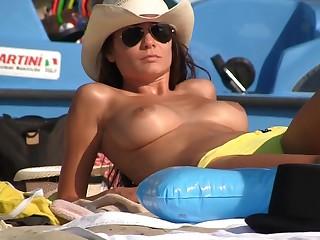 attractive busty brunette aloft someone's skin beach
