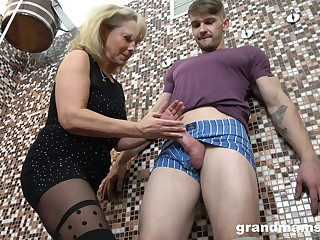 Old woman gives a blowjob and tugjob to young guy in along to sauna